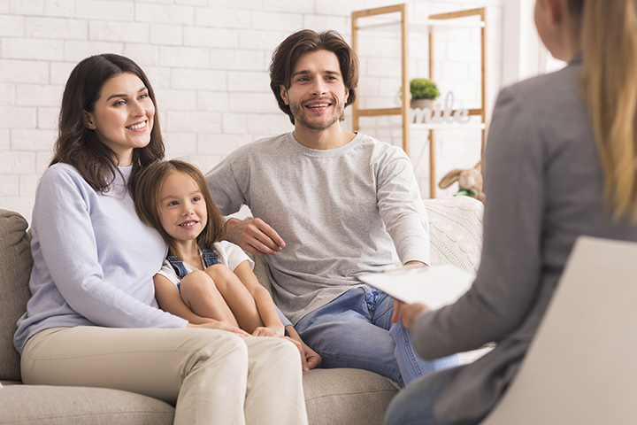 A photo of a young family with their daughter sitting on a couch smiling and talking with their therapist.